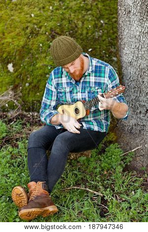 Hipster man with red beard playing a ukulele in the field