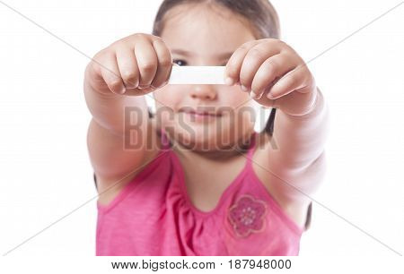Young girl holding a fortune cookie paper with the empty message ready to fill