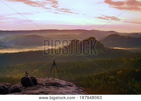 Tripod On The Peak Ready For Photogrphy. Sandstone Peaks Increased From Gold Foggy Background, The F
