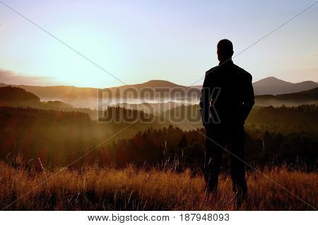 Hiker Stand On Meadow With Golden Stalks Of Grass And Watch Over The Misty And Foggy Morning Valley