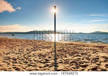 Sun Hidden Behind Blue Pole On Sandy Beach At Sea. Forest Hill On Island In Background