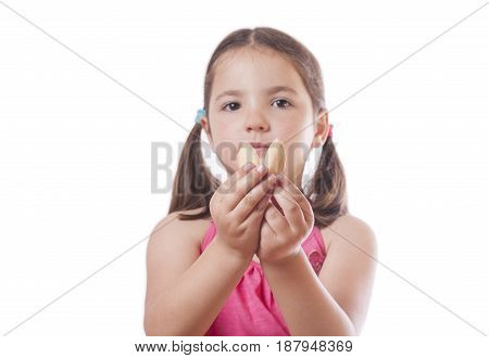 Young girl holding a closed fortune cookie. Isolated over white background