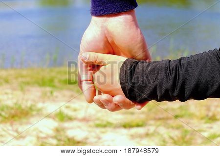 Father's Large Hand Hold Hand Of A Little Kid. Hands In Blue And Black Shirts.