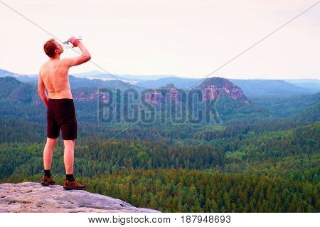 Thirsty Hiker In Black Pants With Bottle Of Water. Sweaty Tired Tourist On The Peak Of Sandstone Roc