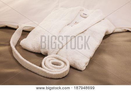 White New Bathrobe On Bed