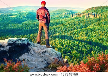 Hiker In Black With Red Baseball Cap On Sharp  Cliff And Watch To Valley. Colorful Summer Day.