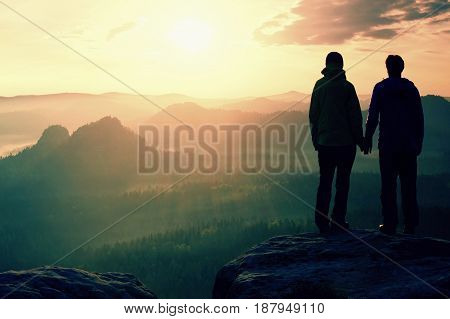 Young Pair Of Hikers Hand In Hand On The Peak Of Rock Empires Park And Watch Over The Misty And Fogg