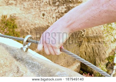 Rock Climber's Hands Hold On Steel Twisted Rope At Steel Bolt Eye Anchored In Rock. Tourist Path Via