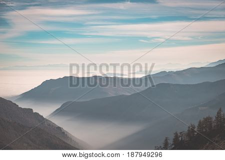 Distant mountain range with fog and mist covering the valleys below.Italian Alps toned image.