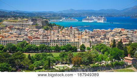 Panoramic view on classical Greek houses buildings architecture of Greece Corfu island capital Kerkyra, white cruise liner ship. Greece holidays vacation touristic tours. Sightseeing view point