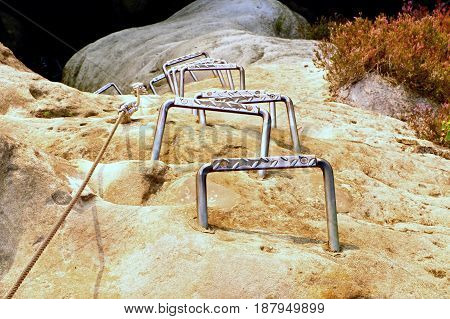 Climbers Metal Ladder Via Ferrata. Iron Twisted Rope Fixed In Block By Screws Snap Hooks. The Rope E