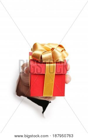 Male hand with gift box punching through the paper
