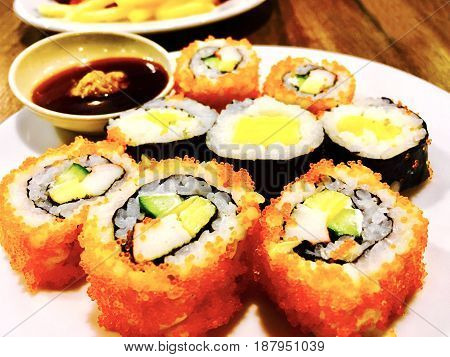 Japanese Cuisine Tamagoyaki Maki or Japanese Omelett Sushi Roll and Tobiko California Roll Served with Soy Sauce and Wasabi.