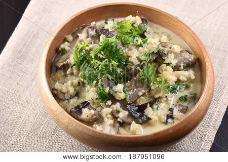 Cauliflower risotto with 3 types of mushroom and parsley in a wooden bowl