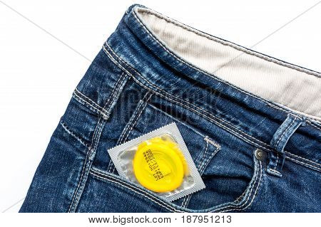 Condoms in package and jeans on white background top view