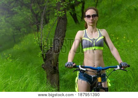 Slender Woman In Sunglasses And With A Bicycle, Posing In The Forest.