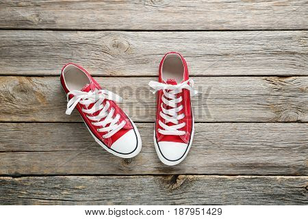 Pair Of Red Sneakers On Grey Wooden Table