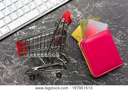 online purchasing with mini trolley, credit cards on dark office desk background top view