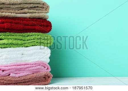 Colorful towels on green background, close up