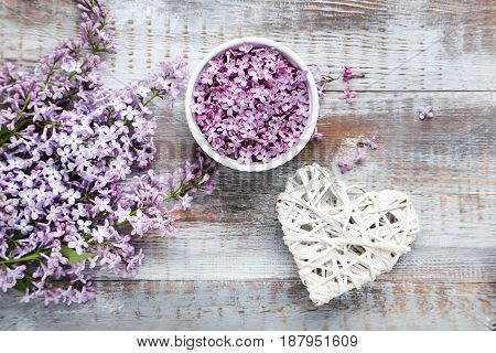Lilac Flowers In Bowl And White Heart On Wooden Table