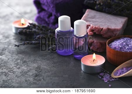 Lavender Oil With Soap, Salt And Flowers On Grey Table