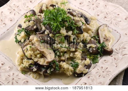 Cauliflower risotto with 3 types of mushroom and parsley on a white dish