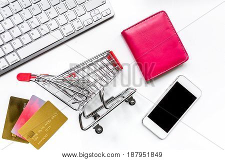online purchasing with mini trolley, cards, phone and wallet on white office desk background top view mock up