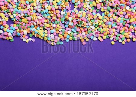 Colorful sprinkles on the purple background, close up