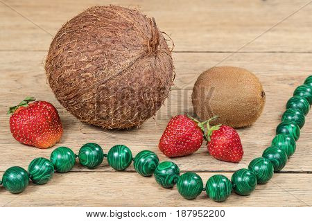 Ripe strawberries, a coconut and kiwi beside the green beads on a wooden table
