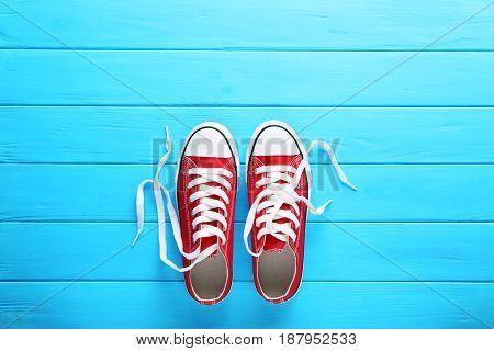 Pair Of Red Sneakers On Blue Wooden Table