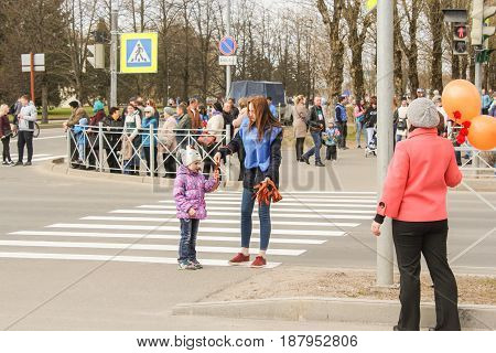 Kirishi, Russia - 9 May, A little girl takes a St. George ribbon, 9 May, 2017. Preparation and conduct of the action Immortal regiment in small cities of Russia.