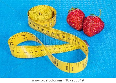 Ripe strawberry with yellow metric tape measure on a blue sports carpet