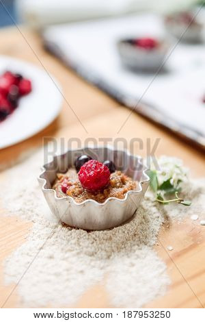 Raw Dough With Berries For Cupcakes Decomposed Into Forms On A Baking Papper On Baking Tray Decorate