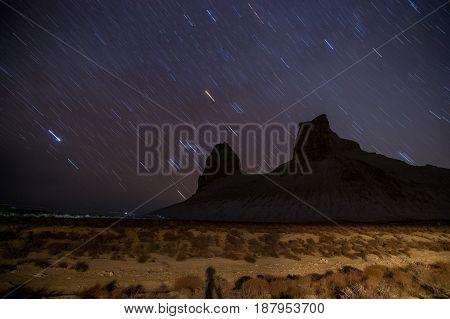 Star trails at night over Boszhira mountain canyon, Mangistau, Mangishlak, Kazakhstan desert in the spring