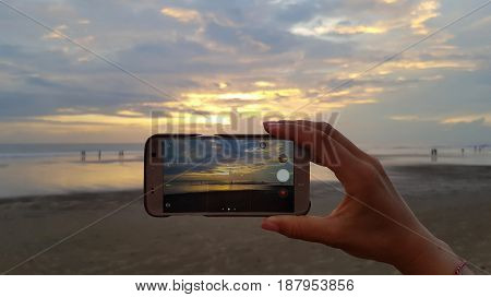 Female hand takes off on your smartphone sunset on the ocean