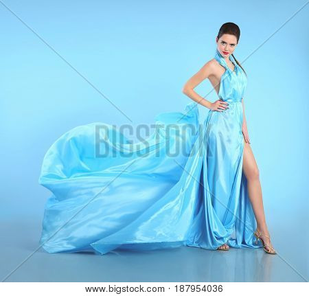 Beautiful Girl In Blowing Blue Dress. Woman In Flying Gown, Silk Fabric Waving On Wind Isolated On S