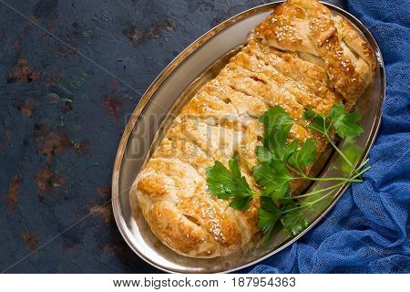 Delicious homemade pie made of puff pastry with cheese and surimi on metal tray. Textured metal background blue gauze napkin. Grunge style