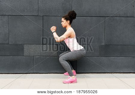 Side view of young athlete squatting at wall