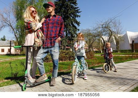 Young family with children on scooters in park during day