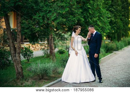 Beautiful couple walking in the park in their wedding day. Sunny weather.