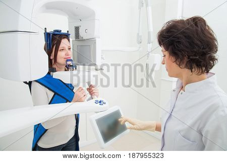 A young dentist taking a panoramic digital X-ray of a patient s teeth