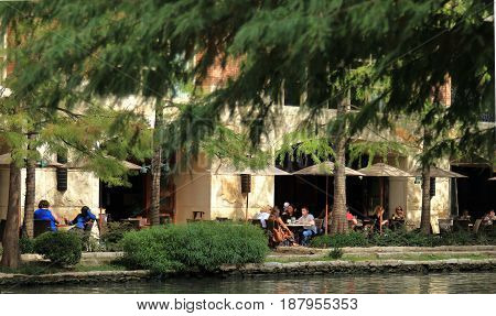 SAN ANTONIO, TEXAS - NOVEMBER 12, 2016: Tourists are eating at the outside cafe on the Riverwalk.