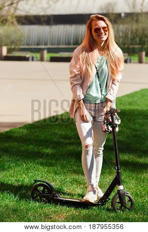 Woman in sunglasses on scooter in park during day