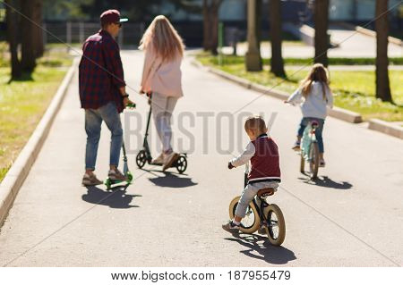 Family with children in active walk on scooters at park