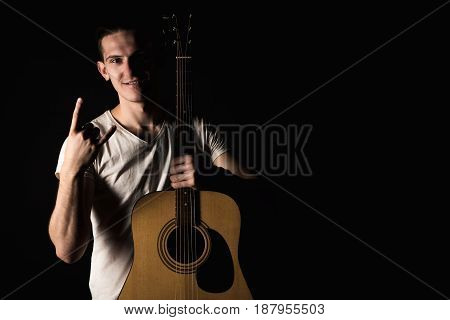 Guitarist, Music. A Young Man Stands With An Acoustic Guitar And Shows His Fingers, On A Black Isola