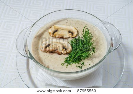 Delicious White Soup With Mushrooms And Herbs, In A Transparent Plate, On A White Tablecloth. Horizo