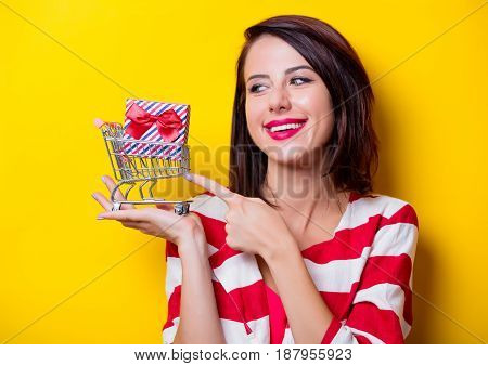 portrait of beautiful young woman with shopping cart and gift in it on the wonderful yellow studio background