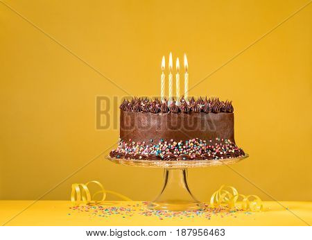 Chocolate birthday cake and candles over yellow background.