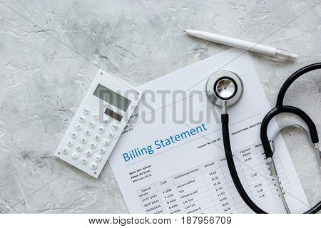 billing statement for for medical service in doctor's office on stone desk background top view