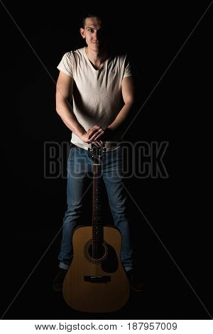 Guitarist, Music. A Young Man Stands With An Acoustic Guitar, On A Black Isolated Background. Vertic